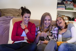 Laughing young girls watching TV together sitting on couch